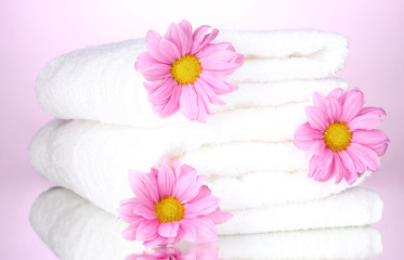 towels and beautiful flowers on pink background