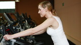 Happy woman using hometrainer in gym