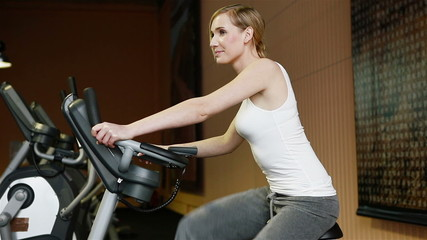 Woman in fitness center on hometrainer