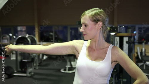 Woman in fitness center using dumbbells