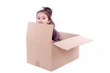 enfant caché dans un carton d'emballage