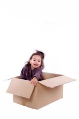 enfant joue dans un carton d'emballage de déménagement