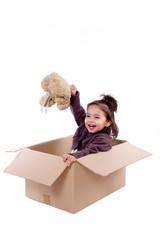 enfant joue dans un carton avec son ours en peluche