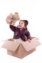 enfant joue dans une boite d'emballage carton avec son ours