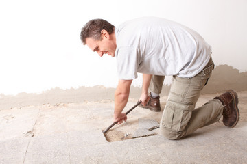 Manual worker disassembling old floor tiles