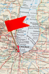 Pin pointing Chicago on map in atlas