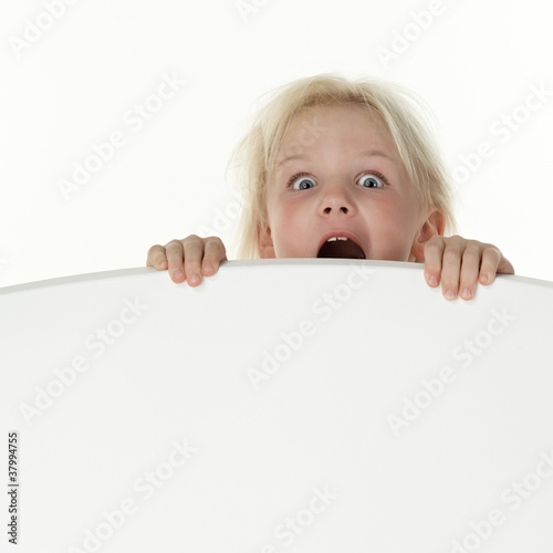 Little girl crying terrified on a white wall with copyspace