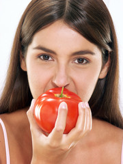 Joven mujer hispana sujetando y mordiendo un tomate fresco.