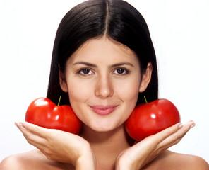Joven mujer hispana sujetando dos tomates frescos.