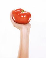 Mano femenina sosteniendo un tomate fresco.