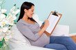 Pregnant woman sitting in a chair writing baby names