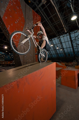 Cyclist standing on grain on back wheel