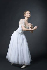 Beautiful ballerina poses in white dress, on pointes.