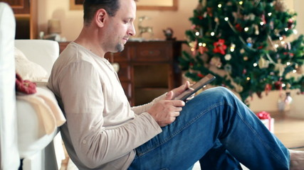 Man with tablet computer, christmas tree in background