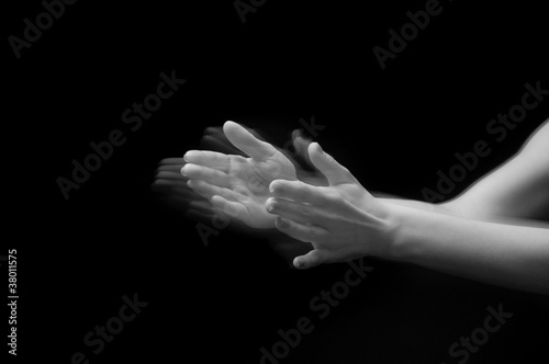Female hands clapping on black, side-view