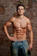 Muscular young naked sexy man posing in blue jeans