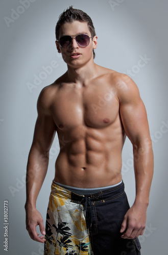 The muscular young naked sexy boy in sunglasses