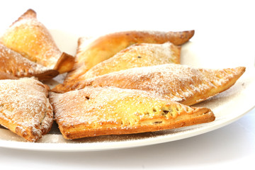 Sweet baked pastry triangles on white plate