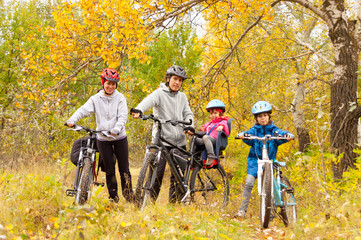 Happy family cycling outdoors, parents with kids on bikes
