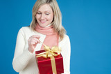 Happy blond woman opening red gift box, over blue background