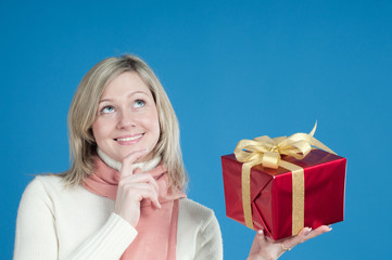 Curious blond young woman holding a present