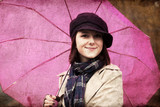 Girl in cloak and scarf with umbrella at park in rainy day. Phot poster
