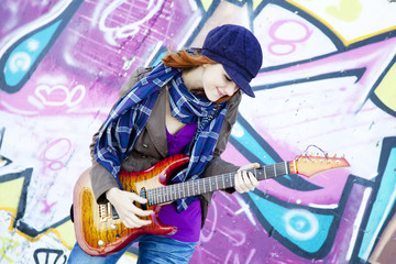 Closeup portrait of a happy young girl with guitar and graffiti