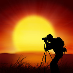 silhouette of photographer with big sun background