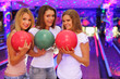 three smiling girls with balls stand in bowling club