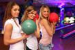 three girls with balls stand in bowling club