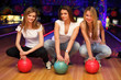 three girls sit with balls in bowling club and smile