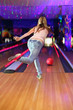 back of girl wearing jeans making throw of ball