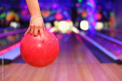 Female hand holding ball before throwing in bowling club