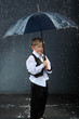 boy dressed in white shirt standing under umbrella in rain
