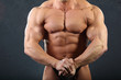 Strong torso and hand muscles of undressed wet bodybuilder