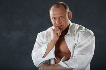 Tanned bodybuilder wearing wet shirt looks thoughtfully