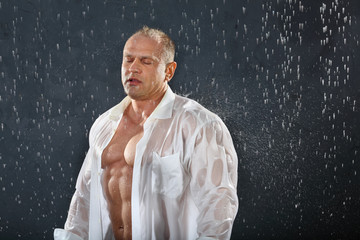 Tanned bodybuilder wearing white wet shirt stands in rain