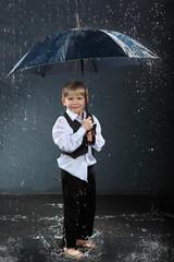smiling boy  standing under umbrella in rain