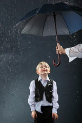smiling boy dressed in white shirt standing under umbrella