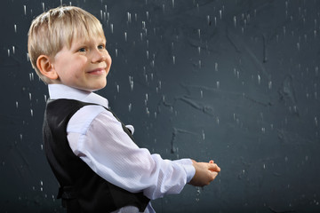 smiling boy dressed in white shirt and black vest stands in rain