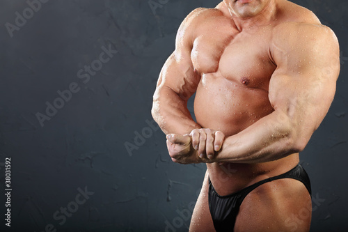 Powerful chest and hand muscles of undressed wet bodybuilder
