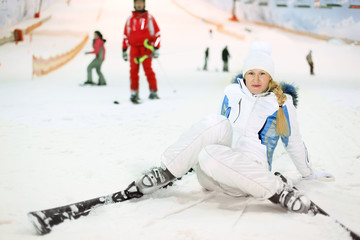 woman dressed in white sports clothes fells on skis