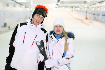 Happy husband and wife dressed in sports clothes stand with skis