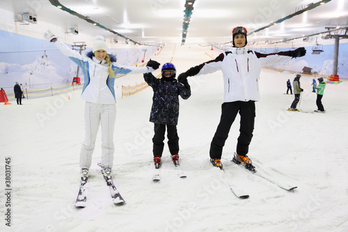 Family dressed in sports clothes standing on skis