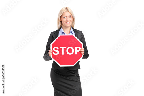 A businesswoman holding a traffic sign stop