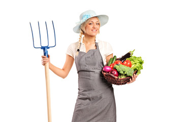 A female farmer holding a pitchfork and basket with vegetables