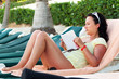 Woman reading book on the Caribbean beach