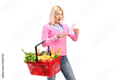 A surprised woman looking at store receipt and holding a shoppin