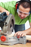 Carpenter or joiner working with power tool poster