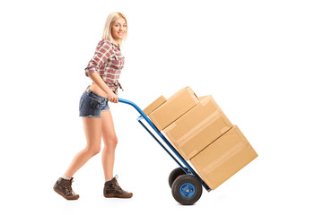 Female manual worker pushing a handtruck with boxes on it